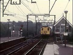 307117 approaches Wickford from Southend in 1985.  The splitting searchlight signal opposite is also history now.