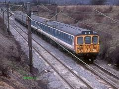 NSE livery 312707 leads another in blue-grey livery past Hatfield Peverel for Clacton in 1987